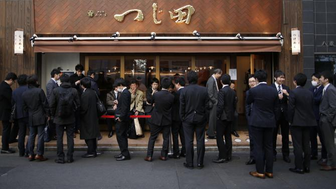 Tokyo businessmen wait in front of a noodle soup restaurant during lunch hour near the headquarters of the Bank of Japan in Tokyo