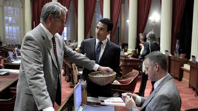 State Sen. Michael Rubio, D-Bakesfield, center, passes out candy to Senators Bill Emmerson, R-Hemet, left, and Anthony Cannella, R-Ceres, before the start of the Senate session at the state Capitol in Sacramento, Calif. Both houses of the Legislature approved the 2012-13 state budget and sent it to the governor. (AP Photo/Rich Pedroncelli)