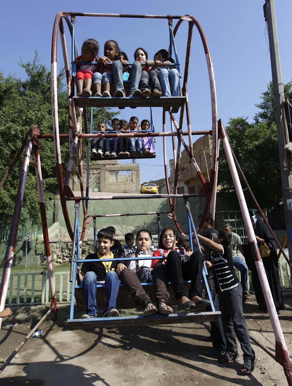 Iraqi children play during Eid al-Adha celebrations in Baghdad's Fadhil neighborhood, Iraq, Saturday, Oct. 27, 2012. A bombing near a playground and other insurgent attacks killed 18 people including several children in Iraq on Saturday, police said. (AP Photo/Khalid Mohammed)