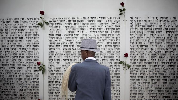 An Ethiopian Jew looks at the wall of names at the Armored Corps memorial for fallen soldiers before a ceremony marking the annual Memorial Day for soldiers and civilians killed in more than a century of conflict between Jews and Arabs, in Latrun near Jerusalem, Israel, Monday, May 5, 2014. Israel came to a standstill on Monday as sirens wailed across the country on its annual Memorial Day for fallen soldiers and victims of terrorism. (AP Photo/Ariel Schalit)