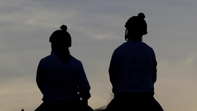 Kentucky Derby winner Orb, right, with exercise rider Jennifer Patterson aboard, is escorted onto the track by Anna Martinovsky at Pimlico Race Course in Baltimore, Friday, May 17, 2013. The Preakness Stakes horse race is scheduled to take place May 18. (AP Photo/Patrick Semansky)