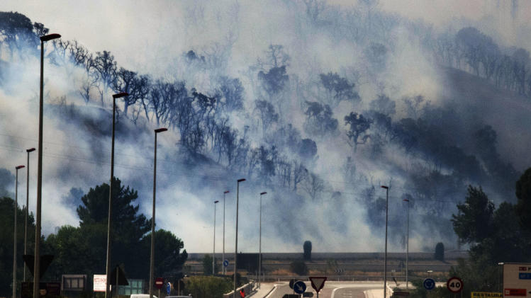 Smoke clings to the forest as flames burn the forest near the highway in La Jonquera, Spain, near the border with France, Sunday, July 22, 2012.  The regional officials said wildfires have burned almost 7,000 hectares (17.297 acres) of forest. (AP Photo/Josep Ribas)