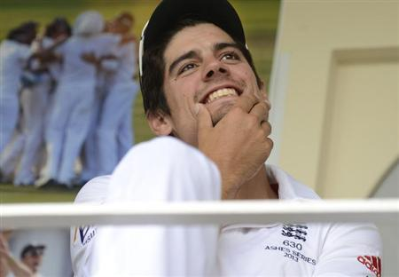 England's captain Alastair Cook smiles while sitting on the dressing room balcony as the second day of the fifth Ashes cricket test match against Australia was delayed by rain at The Oval cricket grou