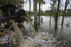 A man looks on as water is pumped out of a canal near 304 Industrial Estate at Srimahaphot district in Prachin Buri