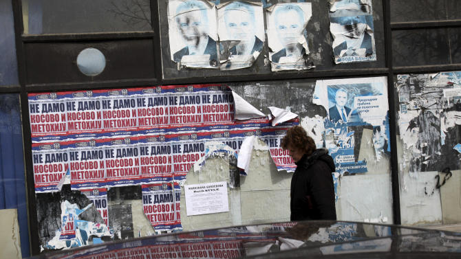 """In this photo taken Saturday, March 30, 2013, a woman passes by the remains of pre-election posters depicting Serbia's President Tomislav Nikolic, top, and banners reading: """"We won't give Kosovo"""" in the northern Serb-dominated part of the ethnically divided town of Mitrovica, Kosovo. Mitrovica, a former mining center in northern Kosovo, was sharply split into Serb and Albanian parts at the end of the Kosovo war in 1999. The town's fate has come into renewed focus as officials from Serbia and Kosovo meet in Brussels on Tuesday in hopes of reaching an agreement that could pave the way for reuniting the divided city. (AP Photo/Darko Vojinovic)"""