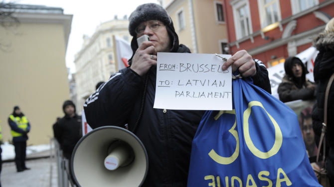 A demonstrator speaks through a megaphone during a protest at the Latvian parliament in Riga, Latvia, Thursday, Jan. 31, 2013. A small group of protesters gathered outside Latvia's Parliament to heckle lawmakers on their way to vote for changes in a law that will allow the Baltic country to adopt the euro, possibly in January 2014. Recent polls suggest a majority of Latvians are against adopting the euro in light of the debt crisis that has afflicted the eurozone for over three years and fears that the Baltic country will have to help bail out struggling countries. (AP Photo/Roman Koksarov)