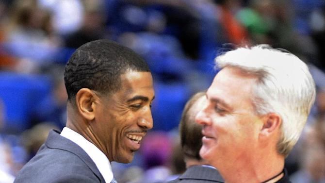 Connecticut coach Kevin Ollie, left, greets an official before the start of his team's NCAA college basketball game against Washington in Hartford, Conn., Saturday, Dec. 29, 2012. Earlier in the afternoon Connecticut officials announced that Ollie had been awarded a new multi-year contract. (AP Photo/Fred Beckham)