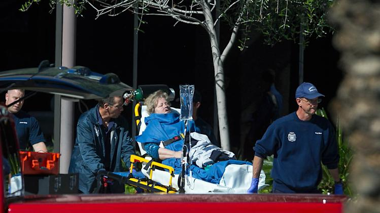 A woman is taken to a paramedic truck from an office building where a shooter opened fire in north central Phoenix on Wednesday, Jan. 30, 2013. (AP Photo/The Arizona Republic, Michael Schennum)