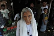 An elderly Muslim Rohingya woman stands by a small stall in the Aung Mingalar quarter, turned into a ghetto after violence wracked the city of Sittwe, capital of Myanmar's western Rakhine state