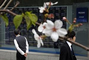 Men pass an electronic stock quotation board, as cherry blossoms bloom, outside a brokerage in Tokyo