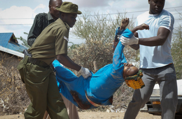 Members of the Kenyan security forces remove the body of a woman killed in the attack at the African Inland Church in Garissa, Kenya Sunday, July 1, 2012. Grenade and gunfire attacks on two Kenyan chu