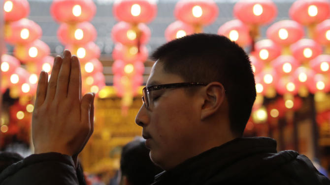 A man prays at a temple in Shanghai, China on Monday Feb. 11, 2013, on the second day of the Chinese Lunar New Year. Chinese celebrate the arrival of the Year of the Snake, according to the Chinese Zodiac. (AP Photo/Eugene Hoshiko)