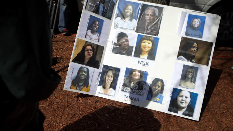 Photos of some of the 35 defendants in Atlanta's school cheating scandal decorate a board as the media wait for the defendants to turn themselves in at Fulton County Jail, Tuesday, April 2, 2013, in Atlanta. The defendants are named in a 65-count indictment that alleges a broad conspiracy involving cheating on standardized tests in Atlanta Public Schools. All 35 defendants must turn themselves in Tuesday. (AP Photo/David Goldman)