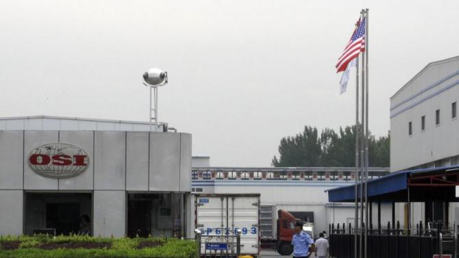 A security personnel stands guard in front of an OSI's food processing plants in Langfang