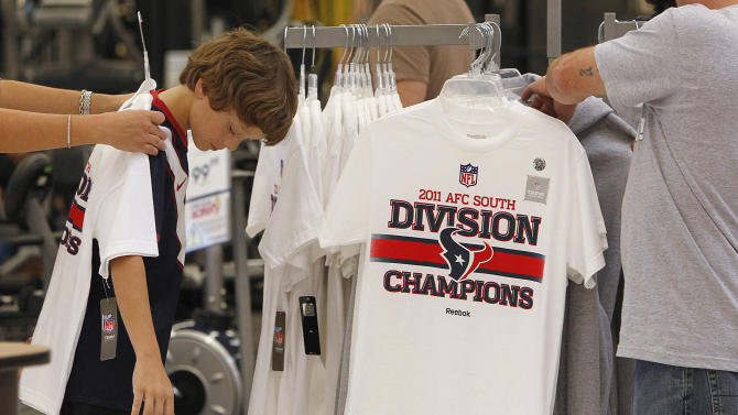 Houston Texans fan Ross Jones, 10, allows his mother to measure a Houston Texans T-shirt for her to purchase on Sunday, Jan. 8, 2012, in Houston. Jones is inspired to try out to be a kicker for his school's team next year, as he watches the playoff games this season. The Texans defeated the Cincinnati Bengals in an NFL football playoff game Saturday. (AP Photo/Houston Chronicle, Mayra Beltran) MANDATORY CREDIT