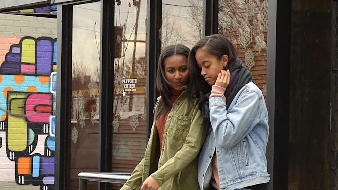 U.S. President Barack Obama's daughters Malia and Sasha depart the Upshur Street Books after visting the store to buy books with their father, in Washington