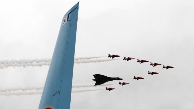 A Vulcan joins the Red Arrow fly pass the airfield to mark the start of Farnborough International Airshow, Farnborough, England, Monday, July 9, 2012. (AP Photo/Sang Tan)