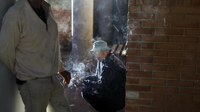 In this May 29, 2013 photo, a patient smokes in the courtyard of the Neuro-Psychiatric Hospital in Asuncion, Paraguay. Under funding plagues the hospital. It recently hit a crisis when the hospital couldn't even buy food and there were no psychiatric drugs for ambulatory patients, only inpatients, according to hospital director Teofilo Villalba. (AP Photo/Jorge Saenz)
