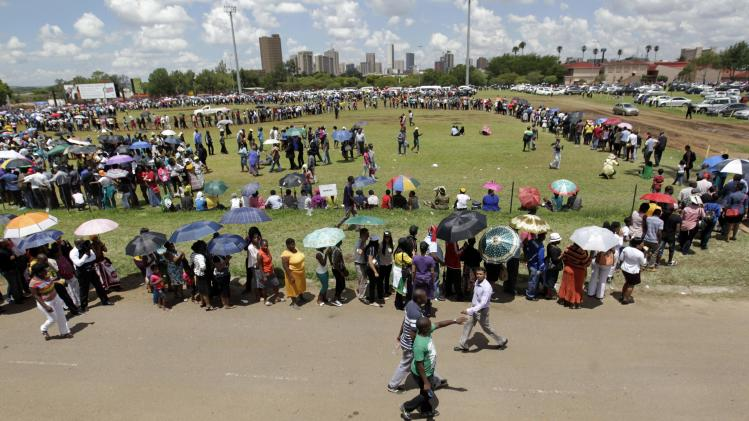 People queue for courtesy buses to ferry them to the Union Buildings to view the body of former South African President Nelson Mandela in Pretoria