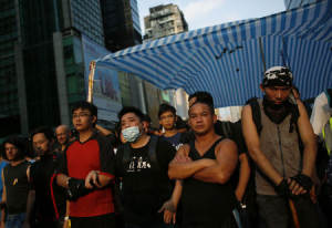 Pro-democracy protesters line up to protect their tent…
