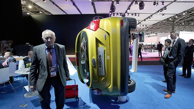 A man walks past a Ford Focus Titanium 1.0 EcoBoost  displayed during the press day at the Paris Auto Show.