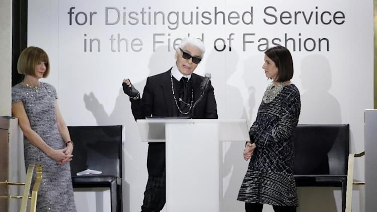 Anna Wintour, left, editor-in-chief of Vogue and Karen Katz, president and CEO of Neiman Marcus, right, watch as Chanel designer Karl Lagerfeld makes comments after receiving a fashion award during an ceremony at the department store, Wednesday, Dec. 11, 2013, in Dallas. (AP Photo/Tony Gutierrez)