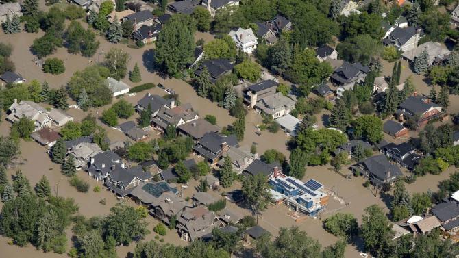This aerial photo shows a flooded downtown Calgary, Alberta, Canada on Saturday, June 22, 2013. The two rivers that converge on the western Canadian city of Calgary are starting to recede after floods devastated much of the southern Alberta province, causing at least three deaths and forcing thousands to evacuate. The flooding forced authorities to evacuate Calgary's entire downtown and hit some of the city's iconic structures hard. The Saddledome, home to the National Hockey League's Calgary Flames, was flooded up to the 10th row, leaving the dressing rooms submerged. (AP Photo/The Canadian Press, Jonathan Hayward)