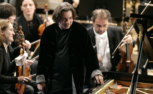 FILE - In this Jan. 31, 2009 file photo, Turkish pianist Fazil Say, center, stands during a performance at the World Economic Forum in Davos, Switzerland. Say appeared in a Turkish court on Thursday, Oct. 18, 2012 to defend himself against charges of offending Muslims and insulting Islam in comments he made on Twitter. (AP Photo/Virginia Mayo, Pool-File)