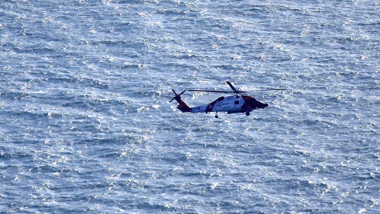 In this aerial photo, a Coast Guard helicopter flies over the area of an explosion and fire on an oil rig in the Gulf of Mexico, about 25 miles southeast of Grand Isle, La., Friday, Nov. 16, 2012. Four people were transported to a hospital with critical burns and two were missing. (AP Photo/Gerald Herbert)