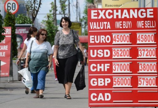 <p>Pedestrians walk past an exchange office's rates notice in Bucharest August 10. The recovery in Romania's economy after two years of severe recession is now coming under threat, analysts warn, victim to the months-long political crisis that has engulfed the EU country</p>