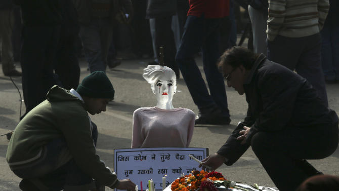 """Indian men place candles in front of a mannequin during a protest in New Delhi, India, Monday, Dec. 31, 2012. A young woman who died after being gang-raped and beaten on a bus in India's capital was cremated privately as millions of grieving, angry residents demanded greater protection for women from sexual violence. The placard reads as, """"Protect women who give birth.""""  (AP Photo/Manish Swarup)"""