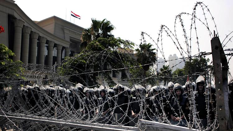 FILE - In this Thursday, June 14, 2012 file photo, Egyptian soldiers stand guard during a protest in front the Supreme Constitutional Court, Egypt's highest court, background, in Cairo, Egypt. Islamists and former members of the military have pushed back Sunday against the decision by Egypt's Supreme Constitutional Court which states that barring members of the armed forces and police from voting goes against the country's first constitution after the ouster of longtime authoritarian leader Hosni Mubarak. (AP Photo/Nasser Nasser, File)