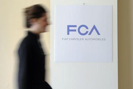 A woman walks past a logo of Fiat Chrysler Automobiles (FCA) in Turin
