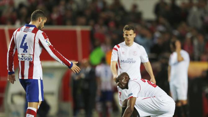 Atletico Madrid's Suarez gives his hand to Sevilla's Mbia after the end of their soccer match in Seville