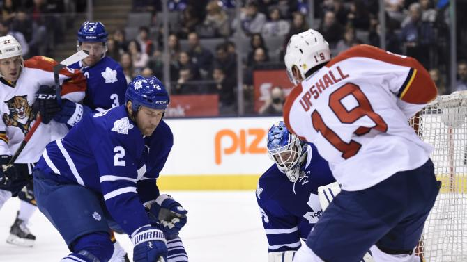Toronto Maple Leafs goalie Jonathan Bernier watches as teammate Eric Brewer (2) and Florida Panthers' Scottie Upshall (19) vie for the puck during the first period of an NHL hockey game Thursday, March 26, 2015, in Toronto. (AP Photo/The Canadian Press, Frank Gunn)