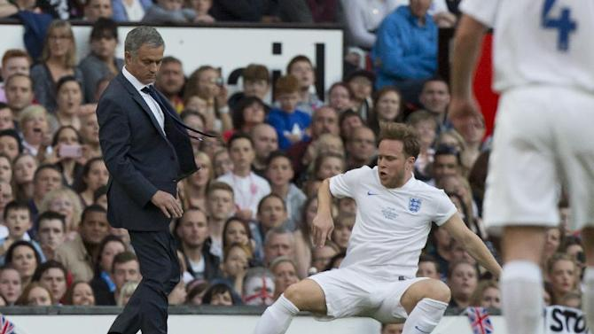 Singer Olly Murs, bottom right, playing for an England team is tripped up by Jose Mourinho manager of a Rest of the World team during the Soccer Aid 2014 charity soccer match at Old Trafford Stadium, Manchester, England, Sunday June 8, 2014