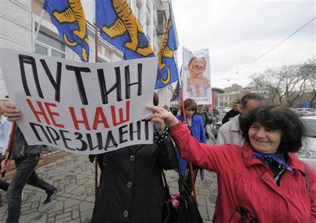 Activists carry placards and flags during an opposition march in Vladivostok