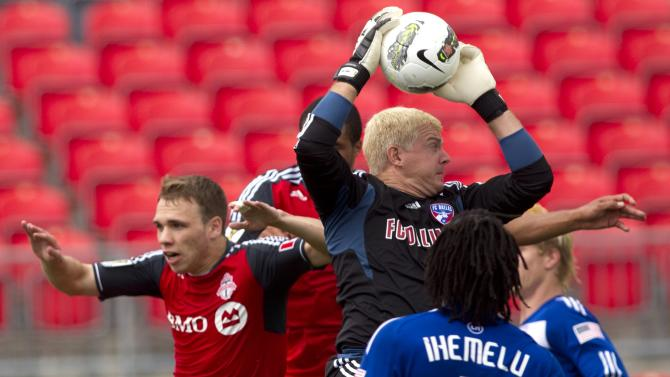 FC Dallas'  goalkeeper Kevin Hartman, center, claims the ball under pressure from Toronto FC 's  Matt Stinson, left,  as Dallas' Ugo Ihemelu looks on during second half  CONCACAF Champions League action in Toronto,  Thursday, Aug. 25, 2011.  (AP Photo/The Canadian Press, Chris Young)