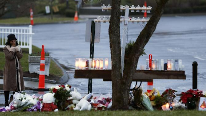 A woman reacts while paying respects for shooting victims at a makeshift memorial at St. Rose of Lima Roman Catholic Church, Sunday, Dec. 16, 2012, in Newtown, Conn. On Friday, a gunman allegedly killed his mother at their home and then opened fire inside the Sandy Hook Elementary School in Newtown, killing 26 people, including 20 children. (AP Photo/Julio Cortez)