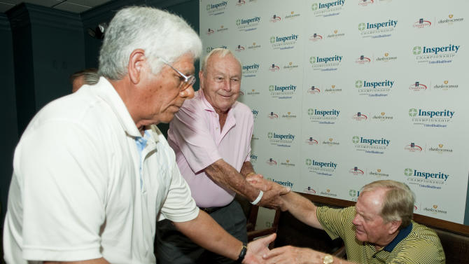 Lee Trevino, left, and Arnold Palmer, center, help Jack Nicklaus, right, out of his chair following a news conference before a Greats of Golf event, Saturday, May 5, 2012, in The Woodlands, Texas. (AP Photo/Dave Einsel)