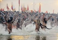Sadhus or holy men run into the Sangham, the confluence of the the Yamuna, Ganges and mythical Sarawati rivers, during the Kumbh Mela in Allahabad on January 14, 2013. The Kumbh Mela, celebrated every 12 years at the conjunction of two sacred rivers on the outskirts of the northern Indian city of Allahabad, drew massive crowds of devotees, ascetics and foreign tourists