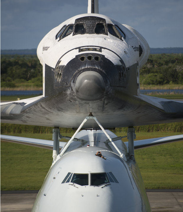 This photo provided by NASA shows a worker at NASA's Kennedy Space Center photographing the space shuttle Endeavour from a hatch on the Shuttle Carrier Aircraft, or SCA, at the Shuttle Landing Facilit