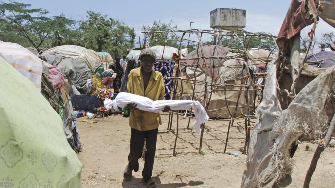 A Somali man from southern Mogadishu carries his dead child in a refugee camp in Mogadishu, Somalia, Tuesday, Sept. 20; 2011. The United Nations World Food Programme is bolstering its nutritional support for malnourished children and mothers in the Horn of Africa. WFP is also expanding its use of cash transfers to help drought-hit families get the food they need. (AP Photo/Farah Abdi Warsameh