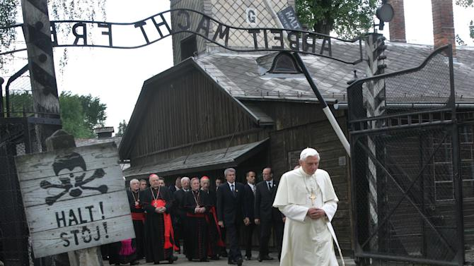 "FILE - In this May 28, 2006 file photo, Pope Benedict XVI walks through the gate of the former Nazi concentration camp Auschwitz in Oswiecim, Poland, to pay his respects to the Holocaust victims. Sign at left reads ""stop"" in German and Polish. Sign above the gate reads ""Arbeit macht frei,"" German for ""work will set you free."" Declaring that he lacks the strength to do his job, Benedict announced Monday Feb. 11, 2013, he will resign Feb. 28 _ becoming the first pontiff to step down in 600 years. (AP Photo/Diether Endlicher)"