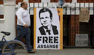 A man walks past posters calling for the freedom of WikiLeaks founder Julian Assange, outside the Ecuadorian embassy in London. Swedish investigators want Assange to answer questions about allegations of rape and sexual assault