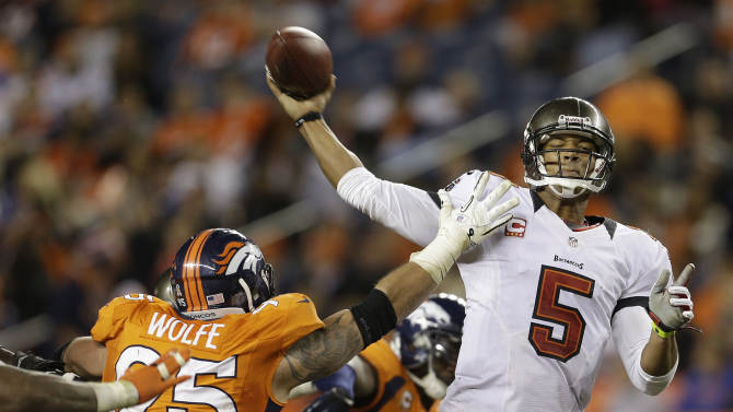 Tampa Bay Buccaneers quarterback Josh Freeman (5) throws against pressure from Denver Broncos defensive end Derek Wolfe (95) in the fourth quarter of an NFL football game, Sunday, Dec. 2, 2012, in Denver. Denver won 31-23 and clinched the AFC West division. (AP Photo/Joe Mahoney)
