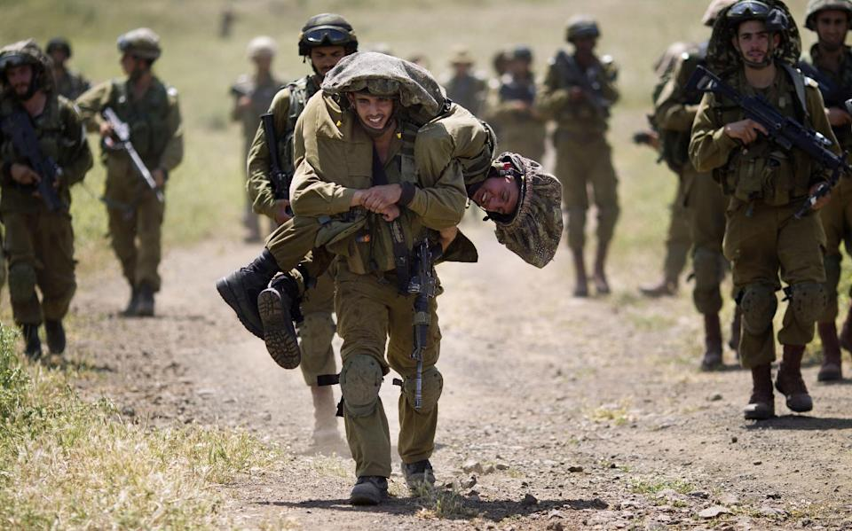 An Israeli soldier carries his mate during a military exercise in the Israeli controlled Golan Heights, near the border with Syria, Tuesday, May 7, 2013. (AP Photo/Ariel Schalit)