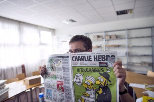 The publisher of French satirical weekly Charlie Hebdo, known as Charb, presents the latest issue to journalists on September 19. Egypt's influential Muslim Brotherhood demanded Thursday that France act against cartoons in the magazine mocking the Prophet Mohammed in the same way as against the topless pictures of Prince William's wife Catherine