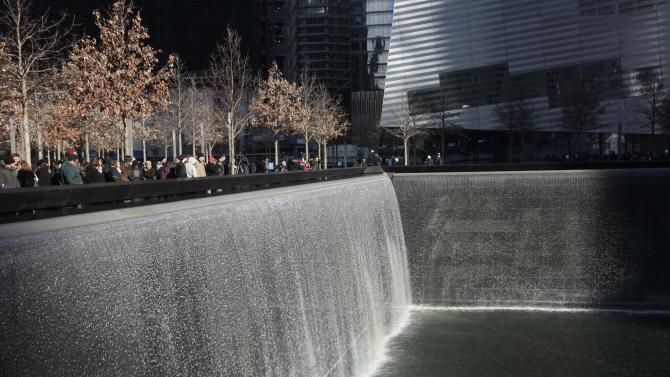Visitors walk around the National September 11 Memorial, Thursday, Dec. 29, 2011 in New York. The memorial announced that it has had a million visitors since the site opened to the public in September. The museum entrance is at right. (AP Photo/Mark Lennihan)