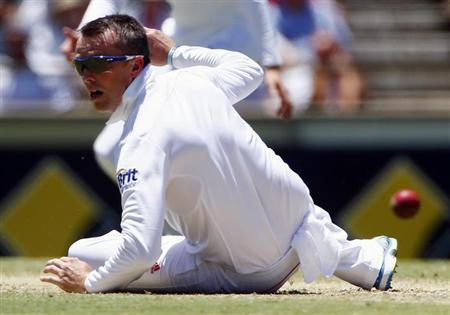 England's Graeme Swann dives to try and stop a shot by Australia's David Warner during the first day of the third Ashes cricket test at the WACA ground in Perth December 13, 2013. REUTERS/Davi